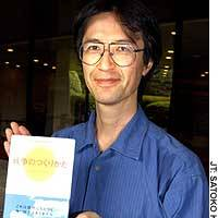 Kazuhiro Imamura, an assistant professor of Japanese language at Hitotsubashi University, holds a hardcover version of 'What Happens Before War?' in Tokyo.