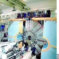 Researchers at a facility of the High Energy Accelerator Research Organization stand near a device that enables them to observe elementary particles decaying to become lighter particles.
