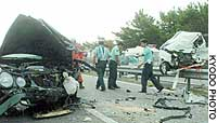 Police inspect the site where a sedan (left) collided head-on with a minicar while heading the wrong way in Hamamatsu, Shizuoka Prefecture.
