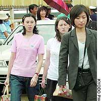 The daughters of repatriated abductee Hitomi Soga -- Mika (left) and Belinda (center) -- arrive Monday at Ryotsu port on Sado Island, Niigata Prefecture, for their first visit to their mother's hometown.