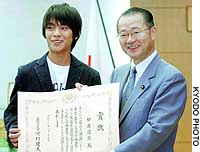 Yuya Yagira, the 14-year-old named best actor at this year's Cannes Film Festival, receives a government award from education minister Takeo Kawamura.