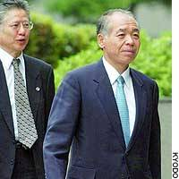 Muneo Suzuki (right) enters the Tokyo District Court for final arguments in his bribery trial.
