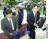 Officials from the Tokyo District Public Prosecutor's Office enter the building housing the office of the Liberal Democratic Party faction that until recently was headed by former Prime Minister Ryutaro Hashimoto.