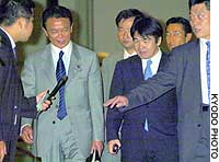 Posts minister Taro Aso (left) and economic and fiscal policy minister Heizo Takenaka are approached by a reporter after attending a meeting on postal privatization in Tokyo.