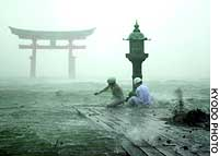 Workers at Itsukushima Shrine in Miyajima, Hiroshima Prefecture, brave Typhoon Songda's winds to examine a lantern pole at the tip of a walkway. Much of the shrine is built over water.