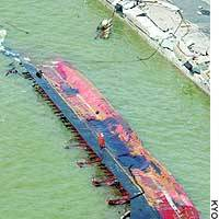 The lumber carrier Blue Ocean lies capsized next to a dock in the city of Hatsukaichi, Hiroshima Prefecture.