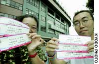 Fans in front of Jingu Stadium in Tokyo show their tickets Saturday to a three-game series between the Yakult Swallows and Hanshin Tigers. All games Saturday and Sunday were canceled after the players' association went on strike for the weekend.
