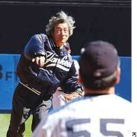 Prime Minister Junichiro Koizumi throws the ceremonial first pitch Sunday before the New York Yankees game against the Boston Red Sox at Yankee Stadium in New York. Yankee outfielder Hideki Matsui served as catcher.