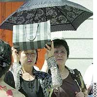 A woman uses a shopping bag to shield herself from the sun in Tokyo's Ginza district.