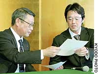 Ryuzo Setoyama (left), chief NPB negotiator, and Atsuya Furuta, head of the players' association, exchange letters of agreement at a press conference in Nagoya on Thursday. The players averted a second strike after reaching an agreement with management that a new team be allowed to join Japanese professional baseball next season.