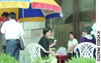 Pyongyang -- Women eat ice cream at a roadside stand here Sept. 3.