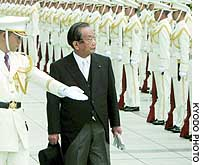 Yoshinori Ono, the new director general of the Defense Agency, is greeted by a Self-Defense Force honor guard at the agency's headquarters in Shinjuku Ward, Tokyo.