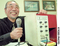 Osaka Karaoke inventor Daisuke Inoue, awarded the Ig Nobel peace prize Thursday in the U.S., shows the first machine at his Osaka office in December 2002.