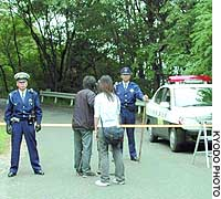 Police officers block public access to a parking lot in Minano, Saitama Prefecture, where seven people were found dead inside a vehicle Tuesday morning.
