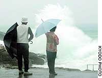 A couple watch high waves in Shirahama, Wakayama Prefecture, Wednesday morning as massive Typhoon Tokage approaches the prefecture.