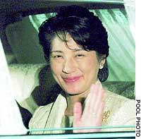 Crown Princess Masako waves from a car as she enters the Imperial Palace for a family dinner to celebrate Empress Michiko's 70th birthday.