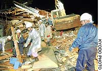Rescuers search for missing people in the rubble of a destroyed house in Ojiya, Niigata Prefecture, at around 4 a.m. Sunday.