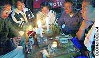 A family forced out of their house in Ojiya, Niigata Prefecture, by the recent earthquakes have to eat by candlelight Monday evening at an evacuation site.