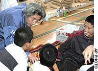 Prime Minister Junichiro Koizumi talks to boys evacuated to the Ote High School gymnasium in quake-stricken Nagaoka, Niigata Prefecture. Below, residents of Ojiya, Niigata Prefecture, make their way along a flooded road destroyed by a series of earthquakes.