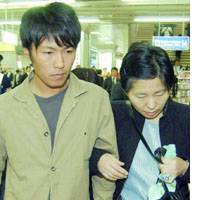 Maki and Setsuko Koda, the elder brother and mother of Shosei Koda, who is being held hostage in Iraq, arrive at JR Kokura Station on Thursday afternoon on their way to meet with members of the media in Tokyo.