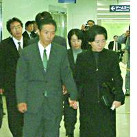 Masumi Koda and his wife, Setsuko, arrive at Fukuoka airport Wednesday evening to receive the body of their son, Shosei, who was slain as a hostage in Iraq.