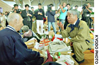 Health minister Hidehisa Otsuji (right) speaks Wednesday to an evacuee at a gymnasium here being used as a shelter. Otsuji was visiting quake-hit areas to assess the needs of residents forced out of their homes.