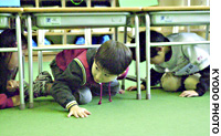 Schoolchildren take cover at the Maekawa Elementary School in Nagaoka, Niigata Prefecture, as the city is shaken by a strong aftershock Thursday morning.