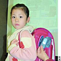 A girl sports a school bag equipped with a built-in global positioning device.