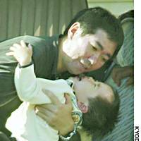 Yuta Minagawa, 2, who survived being buried for four days in a landslide, cries as he is hugged by his father, Manabu, upon arriving Friday at his home in Koide, Niigata Prefecture, after his release from a hospital earlier in the day.