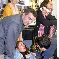 Kurdish asylum-seeker Safiye Kazankiran is aided by compatriot refugee Erdal Dogan during a Tuesday news conference in Tokyo after learning that two of her family members were deported to Turkey.