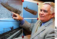 Paul Tidwell, an American shipwreck salvager, shows photos of the Japanese World War II submarine I-52, possibly the most advanced sub of its time, during a recent news conference in Tokyo.