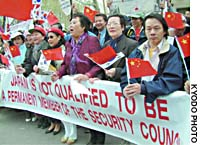 Demonstrators hold a banner protesting Japan's aspirations to become a permanent member of the U.N. Security Council during a rally Friday in front of U.N. headquarters.