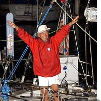 Minoru Saito raises his arms in triumph aboard his sloop, Shuten-dohji II, at Koajiro Bay in Misaki, Kanagawa Prefecture, on Monday evening after completing a nonstop unassisted circumnavigation.