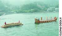 A replica of an ancient boat towing a raft carrying a stone coffin sets off Sunday morning on a monthlong experimental journey to Osaka.
