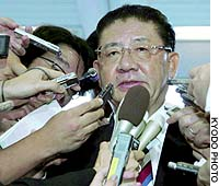 Taku Yamasaki, a senior Liberal Democratic Party member, speaks to reporters Wednesday afternoon in Tokyo after a prosecution inquest committee said he should be charged in connection with a shady political donation.