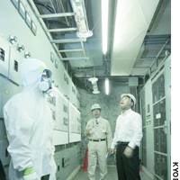 Transport Minister Kazuo Kitagawa (right) inspects walls and a ceiling with asbestos insulation at a former Japan Post branch in Tokyo's Otemachi district.