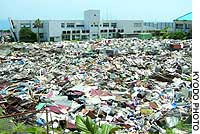 The playground at Tsubota Junior High School on Miyake Island has been turned into a sea of garbage, filled with household equipment rendered unusable during the islanders' 4 1/2-year evacuation.