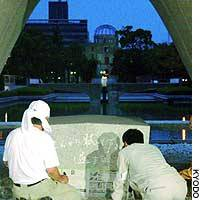Workers begin repairing a vandalized monument for atomic bomb victims Monday at Hiroshima's Peace Memorial Park.