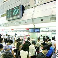 People wait for flights to resume at Haneda airport in Tokyo on Tuesday.