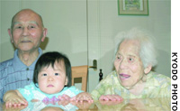 Yoichi and Kazono Gomi pose with their great-grandson, Seiya, at their home in Yokohama.