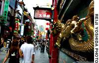 A couple stroll the main street of Yokohama's Chinatown and its ornate eateries on July 31.
