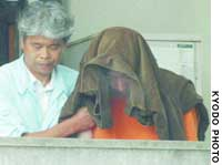 Hiroshi Maeue, with a jacket over his head, is escorted Saturday morning out of a police station in Kawachi Nagano, Osaka Prefecture, on his way to be questioned by prosecutors.