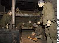 Hungry Japanese soldiers watch a fellow inmate distribute bread at a Siberian prison camp after World War II in this diorama at Exhibition and Reference Library for Peace and Consolation ... Remembering the Misery of War, in Shinjuku Ward, Tokyo.