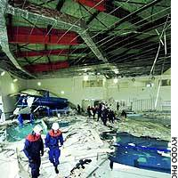 Rescue workers in Sendai stand amid the debris of a ceiling that collapsed Tuesday at an indoor swimming pool following a strong earthquake.