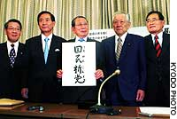 Former Lower House Speaker Tamisuke Watanuki holds a sign bearing the name of his new party -- Kokumin Shinto -- at a news conference Wednesday in Tokyo with colleagues (from left) Kensei Hasegawa, Hisaoki Kamei, Hideaki Tamura and Shizuka Kamei.