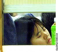 Passengers catch some shut-eye early Wednesday on a train provided by East Japan Railway Co. at JR Tokyo Station for people who missed their connections after the Tohoku Shinkansen Line service was disrupted by the earthquake the day before.