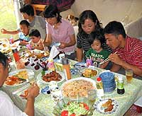 Kazuyuki and Naomi Toyama and their son, Keisuke (trio at right), eat lunch with other mothers and kids at Yokohama Family House in July. | PHOTO COURTESY OF YOKOHAMA FAMILY HOUSE