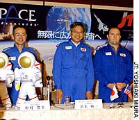 JTB Corp. Managing Director Shinichi Shimizu, flanked by Eric Anderson, the CEO of Space Adventures Ltd. of the United States, and Toyoyuki Nakamura, a JTB official in charge of space tours, unveils Japan's first space tour packages Thursday at a Tokyo hotel.