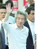 Prime minister and Liberal Democratic Party President Junichiro Koizumi waves Saturday to a crowd in Kobe, while Katsuya Okada, head of the Democratic Party of Japan, makes a point during a speech in the city of Fukui.