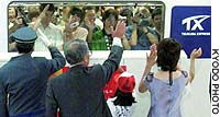 Railway officials and others send off the first Tsukuba Express line train as it departs Wednesday morning from Tsukuba, Ibaraki Prefecture, bound for the Akihabara district in Tokyo.